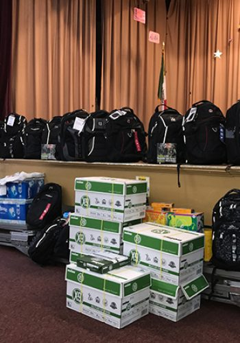 """Erroll Reese & Kevin """"K-Mac"""" McClendon, hosts of The Sports Radio Show, present school supplies to Burton Elementary School in Durham at their first ever Backpacks for Teachers donation event in August 2017."""
